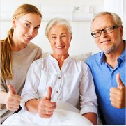 caregiver and elderly couple doing a thumbs up