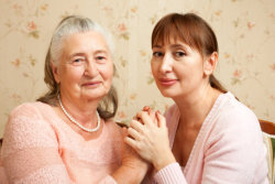 caregiver and old woman holding hands